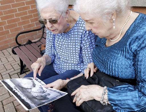 "In this Aug. 21, 2018 photo, Jean Harrison of Algonquin, left, and Jane Umbarger of  McHenry, known as the ""incubator twins"", look at a photo of their infancy as they talk about their experiences McHenry, Ill. The twin sisters, both 84, were among hundreds of premature infants who were placed in incubators at the Century of Progress expo in Chicago in 1933 and 1934. They also had a double wedding in 1953, which drew national attention. The sisters are featured in a new book by Dawn Raffel, titled ""The Strange Case of Dr. Couney: How a Mysterious European Showman Saved Thousands of American Babies.""(Matthew Apgar/Northwest Herald via AP)"