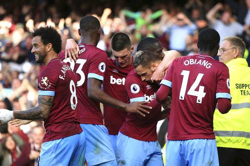 West Ham United's Marko Arnautovic, centre, celebrates scoring his side's third goal of the game with teammates, during the English Premier League soccer match between Everton and West Ham United, at Goodison Park, Liverpool, England, Sunday Sept. 16, 2018. (Peter Byrne/PA via AP)