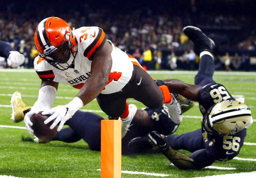 Cleveland Browns running back Carlos Hyde (34) scores a touchdown past New Orleans Saints linebacker Demario Davis (56) during the second half of an NFL football game in New Orleans, Sunday, Sept. 16, 2018.