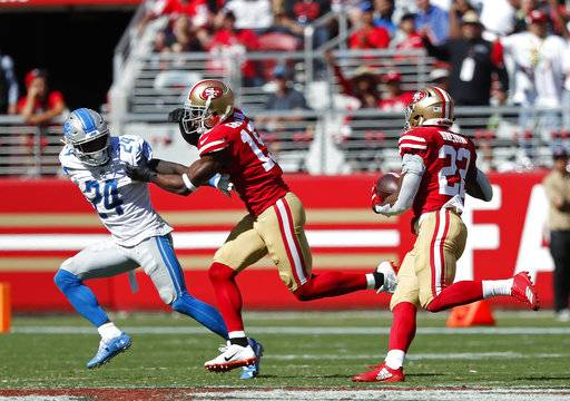 San Francisco 49ers running back Matt Breida goes on a 66-yard touchdown run as wide receiver Pierre Garcon blocks Detroit Lions defensive back Nevin Lawson (24) during the second half of an NFL football game in Santa Clara, Calif., Sunday, Sept. 16, 2018.