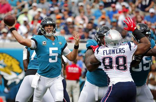 Jacksonville Jaguars quarterback Blake Bortles (5) throws a pass as he is pressured by New England Patriots defensive end Trey Flowers (98) during the first half of an NFL football game, Sunday, Sept. 16, 2018, in Jacksonville, Fla.