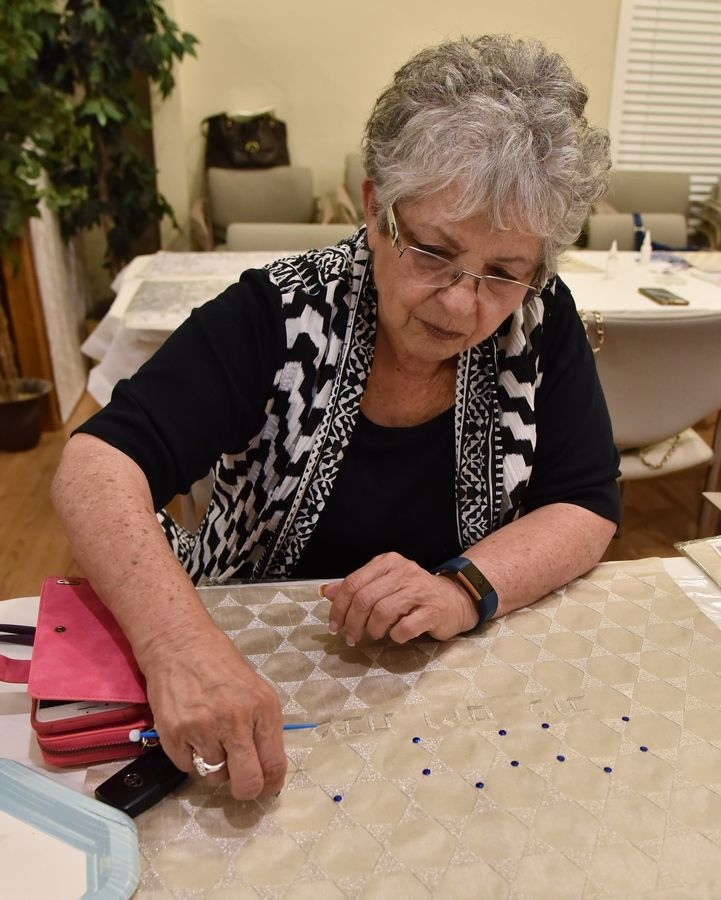 Gloria Katz, of Hoffman Estates, glues beads to the Star of David design on a fabric cover for challah bread for Yom Kippur at the Chabad Jewish Center in Elgin.
