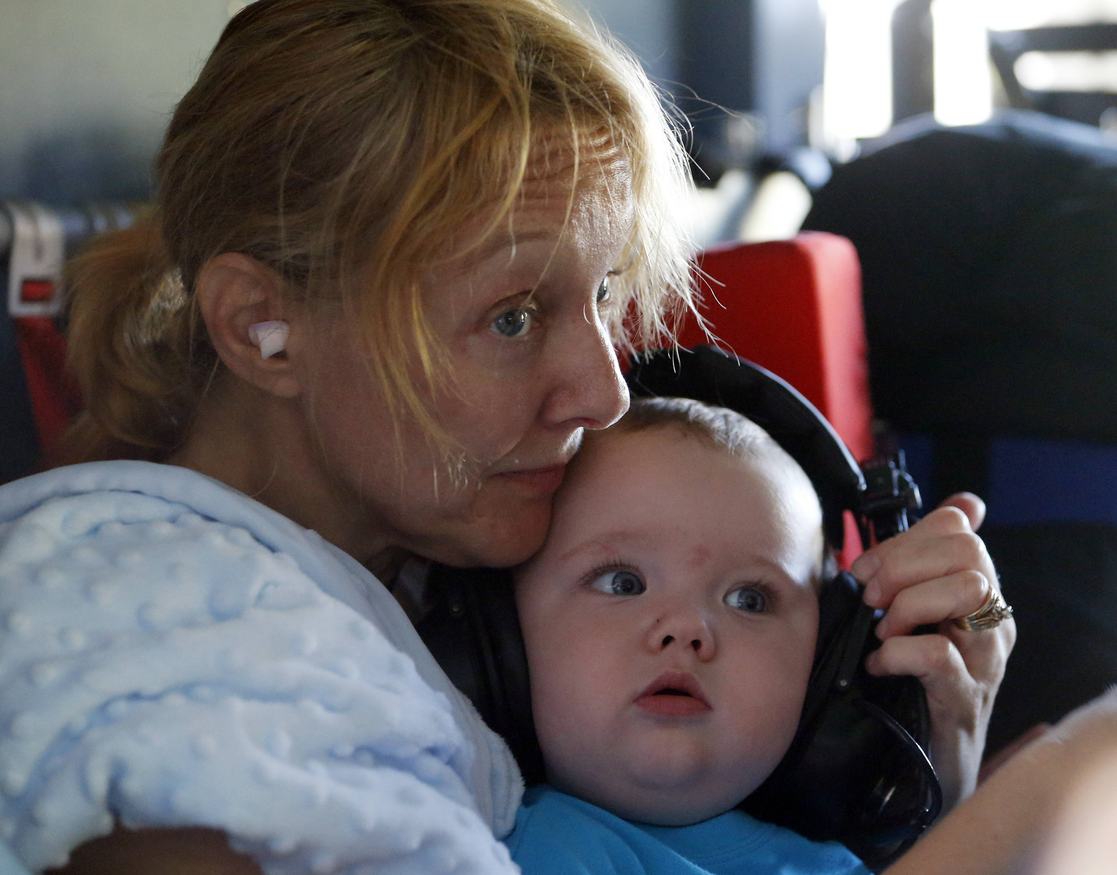 Catherine Riggs, holds her grandson Luke Humphrey as she listens to a briefing aboard a U.S. Coast Guard helicopter in Burgaw , N.C., Tuesday, Sept. 18, 2018. The family was rescued by the crew and taken to a shelter in Wilmington. (AP Photo/Steve Helber)