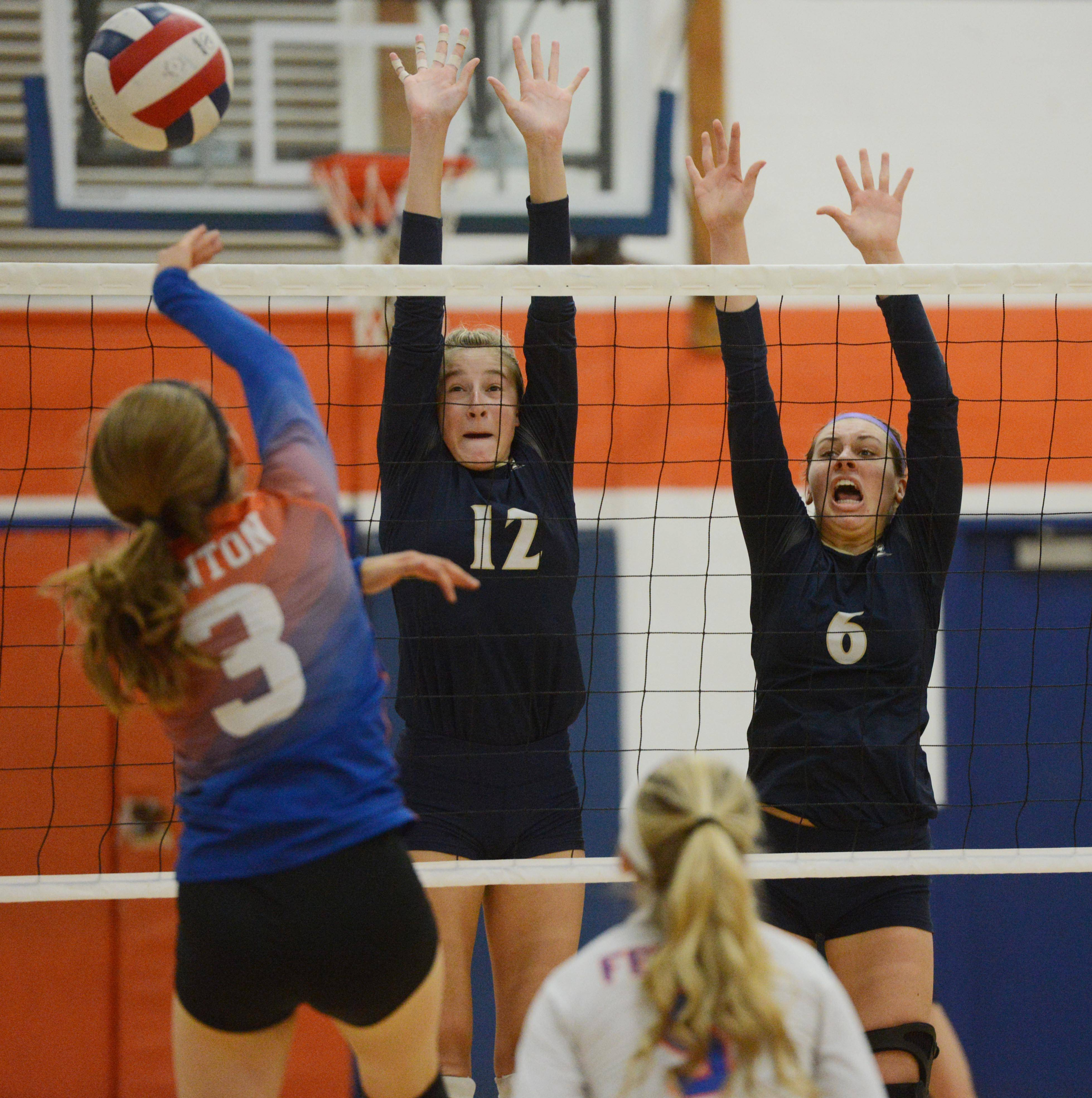 Fenton's Julia Kaspari, left, tries to hit the ball past IC Catholic Prep's Claire Wagner, middle, and Kristen Brachmann during Tuesday's girls volleyball match in Bensenville.