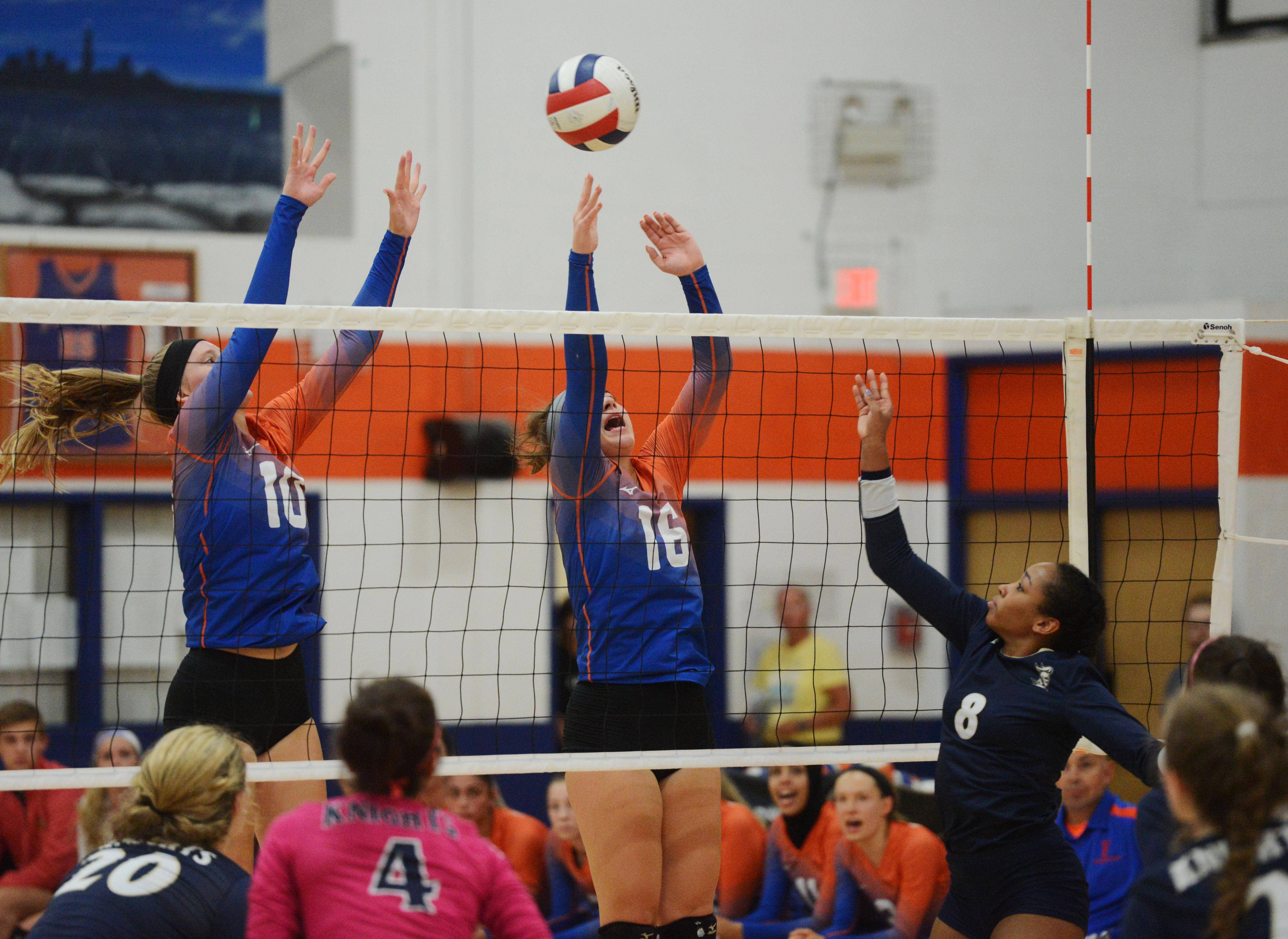 IC Catholic Prep's Maya Stovall, right, tries hit the ball past Fenton's Julianna Krebasch, left, and Agata Kukielko during Tuesday's girls volleyball match in Bensenville.