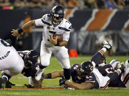 Chicago Bears defensive end Akiem Hicks (96) tries to tackle Seattle Seahawks quarterback Russell Wilson (3) during the first half of an NFL football game Monday, Sept. 17, 2018, in Chicago. (AP Photo/Nam Y. Huh)