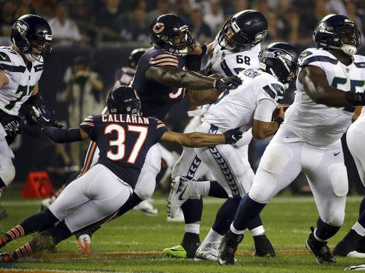 Seattle Seahawks quarterback Russell Wilson (3) gets sacked by Chicago Bears linebacker Aaron Lynch (99) as he is pressured by Lynch and cornerback Bryce Callahan (37) during the first half of an NFL football game Monday, Sept. 17, 2018, in Chicago.