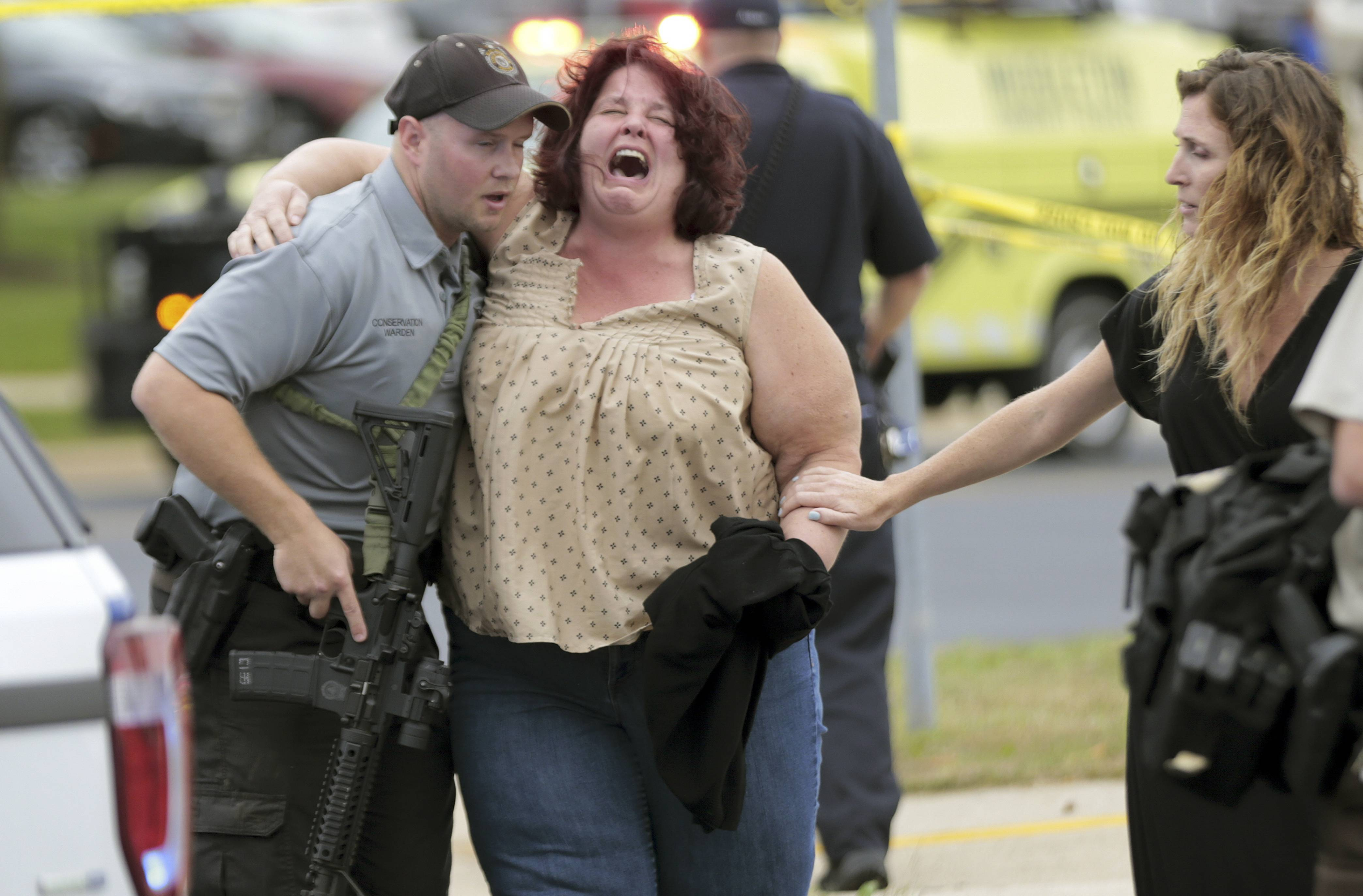 A women is escorted from the scene of a shooting at a software company in Middleton, Wis., Wednesday, Sept. 19, 2018. Four people were shot and wounded during the shooting in the suburb of Madison, according to a city administrator. (Steve Apps/Wisconsin State Journal via AP)