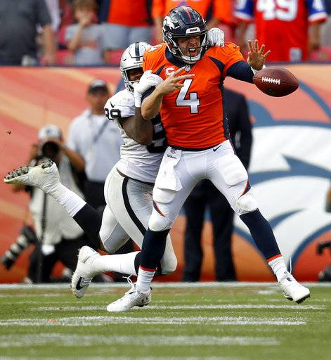 Denver Broncos quarterback Case Keenum (4) fumbles under pressure from Oakland Raiders defensive end Arden Key (99) during the second half of an NFL football game, Sunday, Sept. 16, 2018, in Denver. The Broncos recovered the ball in their 20-19 win. (AP Photo/David Zalubowski)