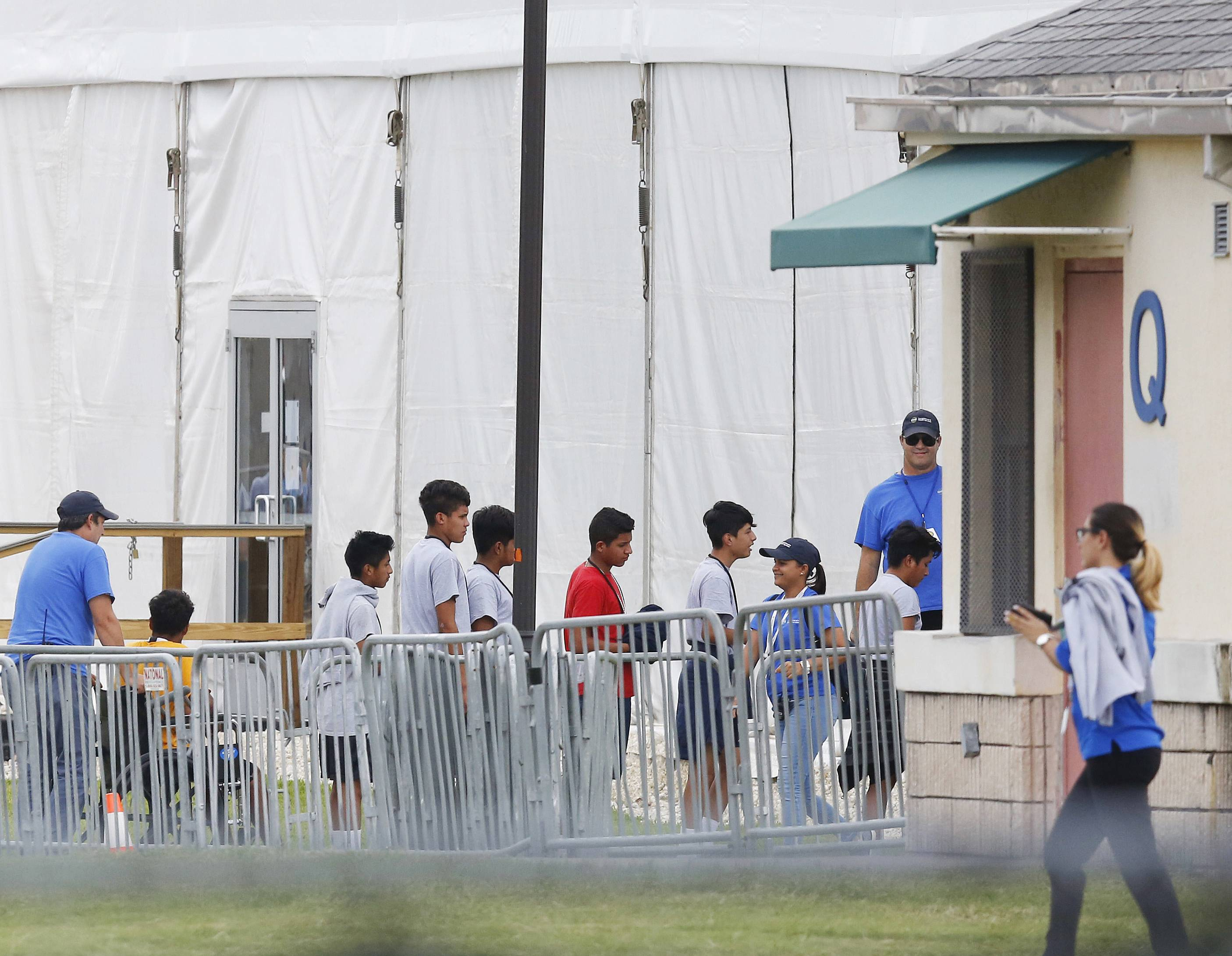 FILE — In this June 20, 2018, file photo, Immigrant children walk in a line outside the Homestead Temporary Shelter for Unaccompanied Children a former Job Corps site that now houses them in Homestead, Fla. A Senate subcommittee has found that federal officials for the second time lost track of nearly 1,500 migrant children earlier this year after a government agency placed the minors in the custody of adult sponsors in communities nationwide.