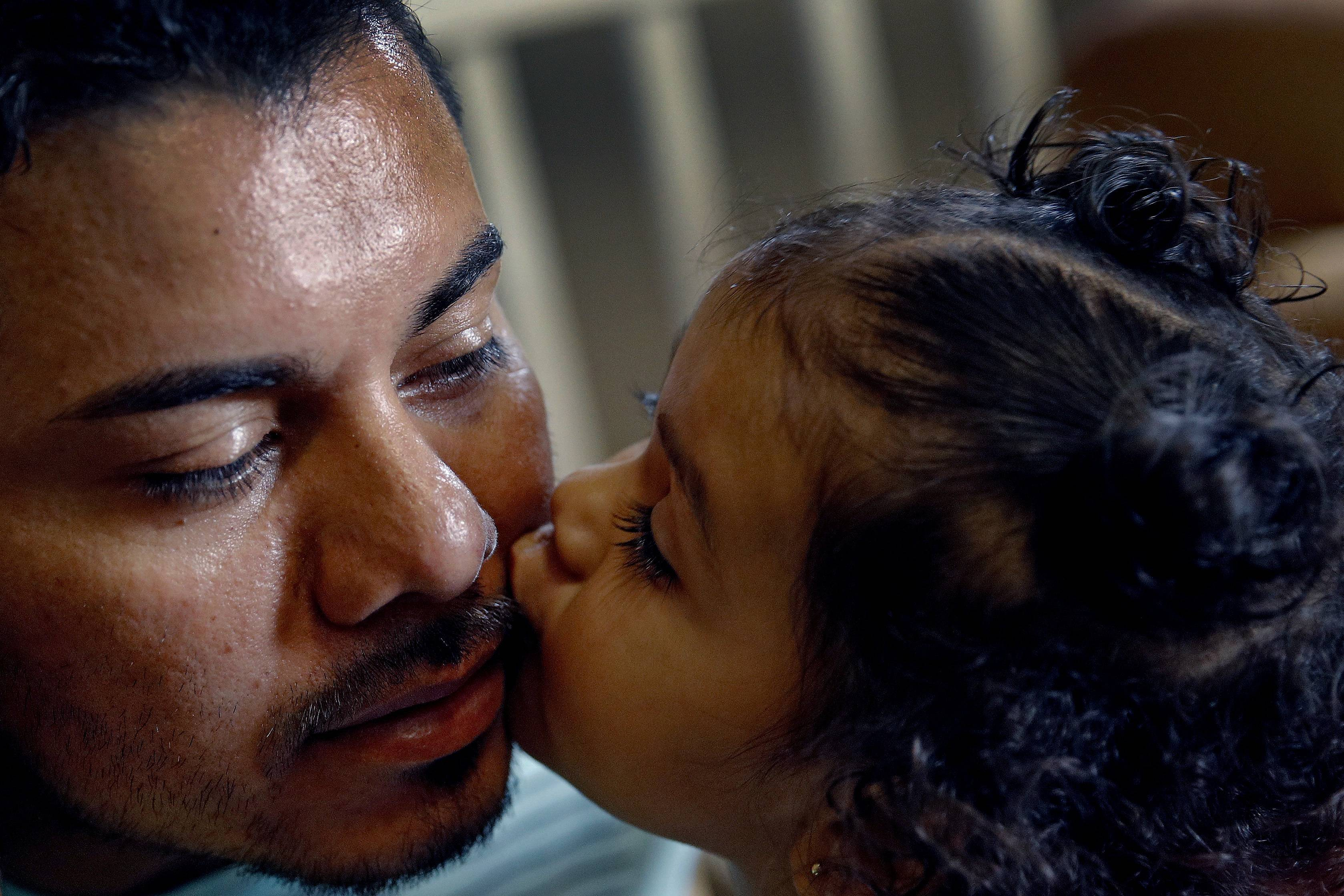In this photo taken Tuesday, Aug. 28, 2018, Louis Alberto Enamorado Gomez gets a kiss from his daughter, Jeydi, 1, at their home in Grandview, Mo. Living in the U.S. since 2005, Gomez is fighting a deportation order stemming from a 2012 DUI charge because he fears what his removal would mean for his seven children, all U.S. citizens for whom he is the sole provider.