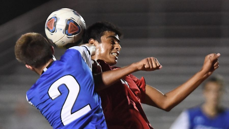 Geneva's Ethan Hipp and Batavia's Eddie Torres compete for the ball Thursday at St. Charles East High School.