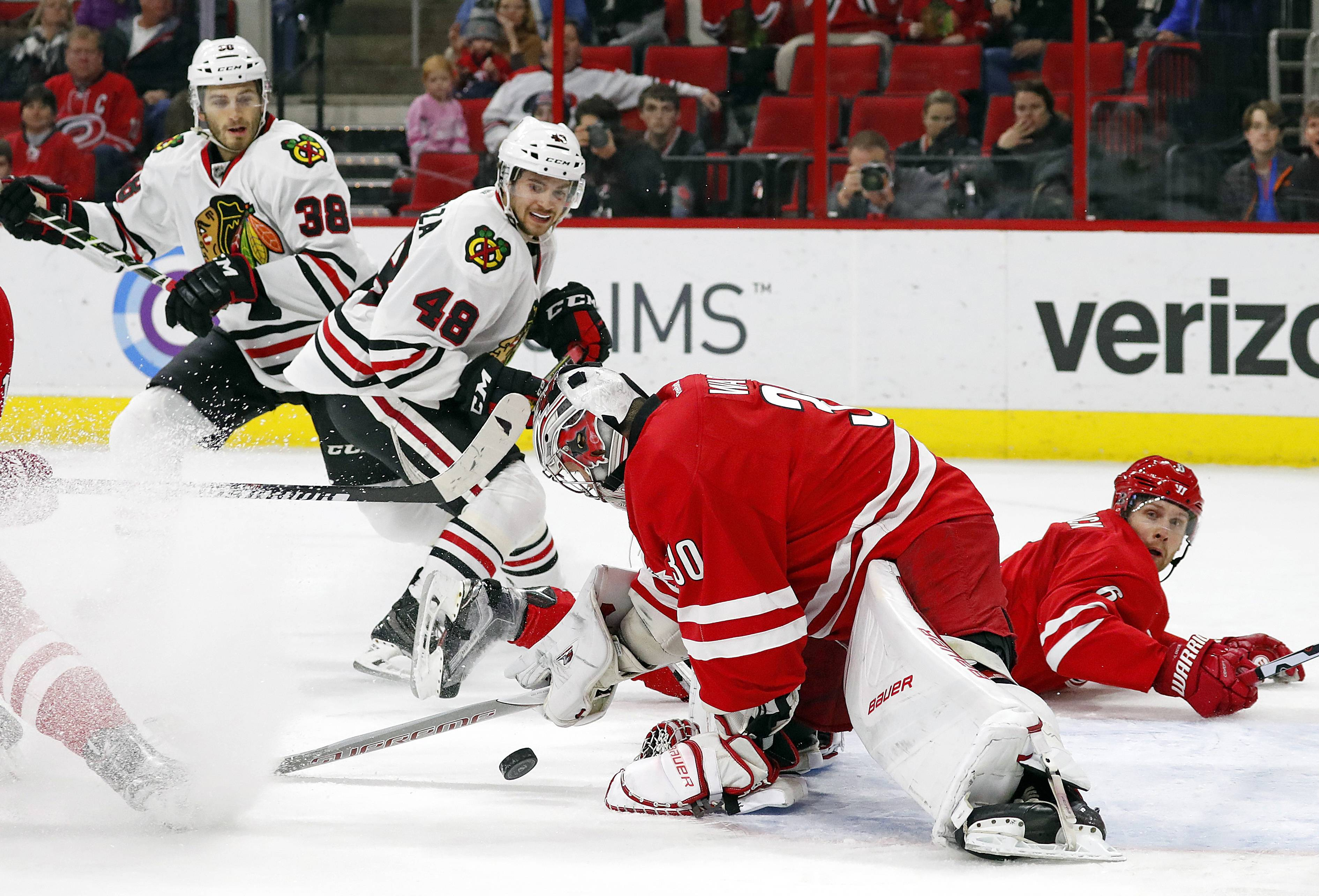 Carolina goalie Cam Ward (30) freezes the puck after it is shot by Blackhawks' Vinnie Hinostroza (48) with Hawks Ryan Hartman (38) looking on during a 2016 game against the Hurricanwes. As each day comes off the calendar with Corey Crawford unable to join his teammates for practice, it's looking more and more like Ward will start in net when the Blackhawks open their season at Ottawa on Oct. 4.