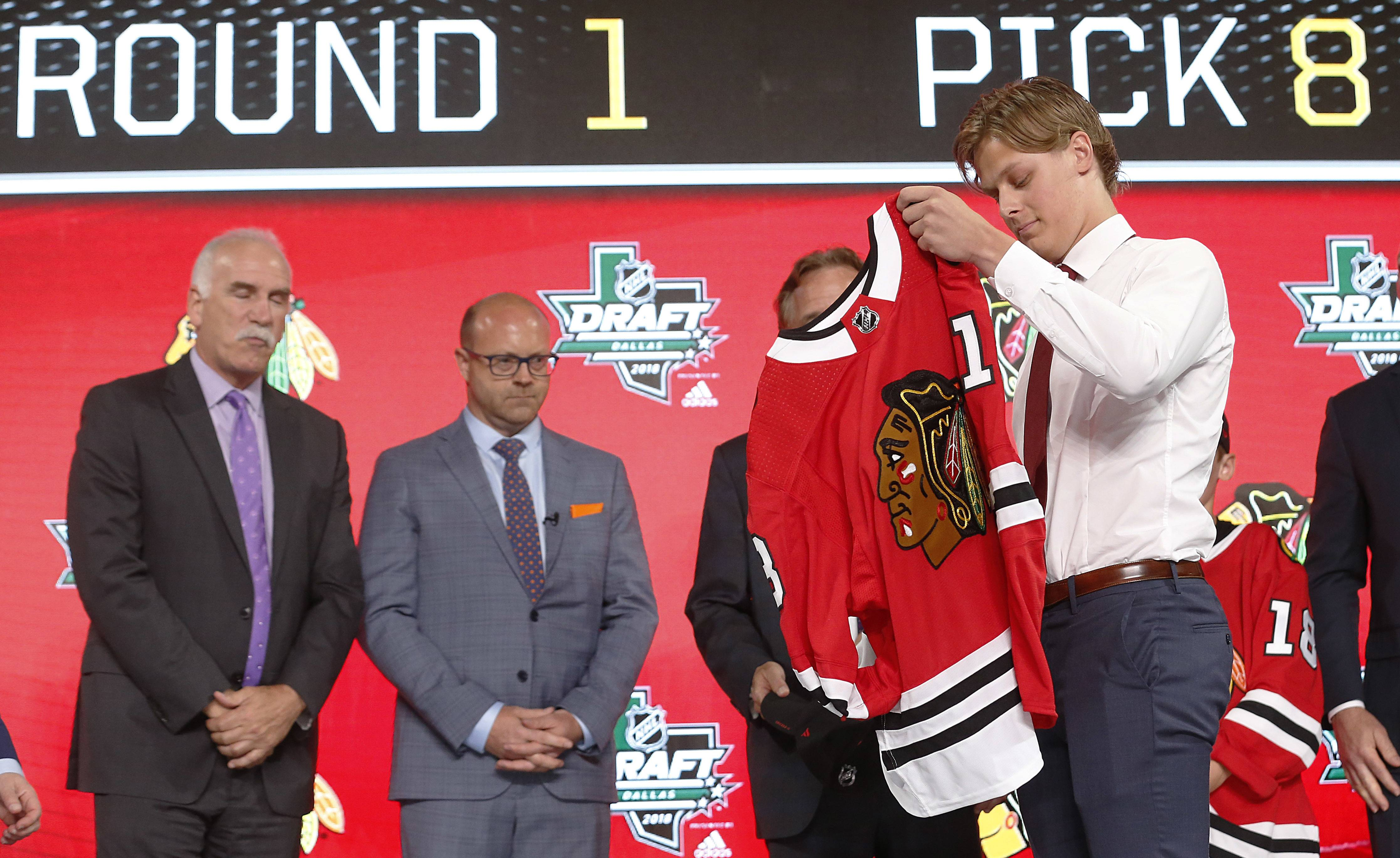 Adam Boqvist tries on a Blackhawks jersey after being selected in the June draft. Coach Joel Quenneville and General Manager Stan Bowman are at left.