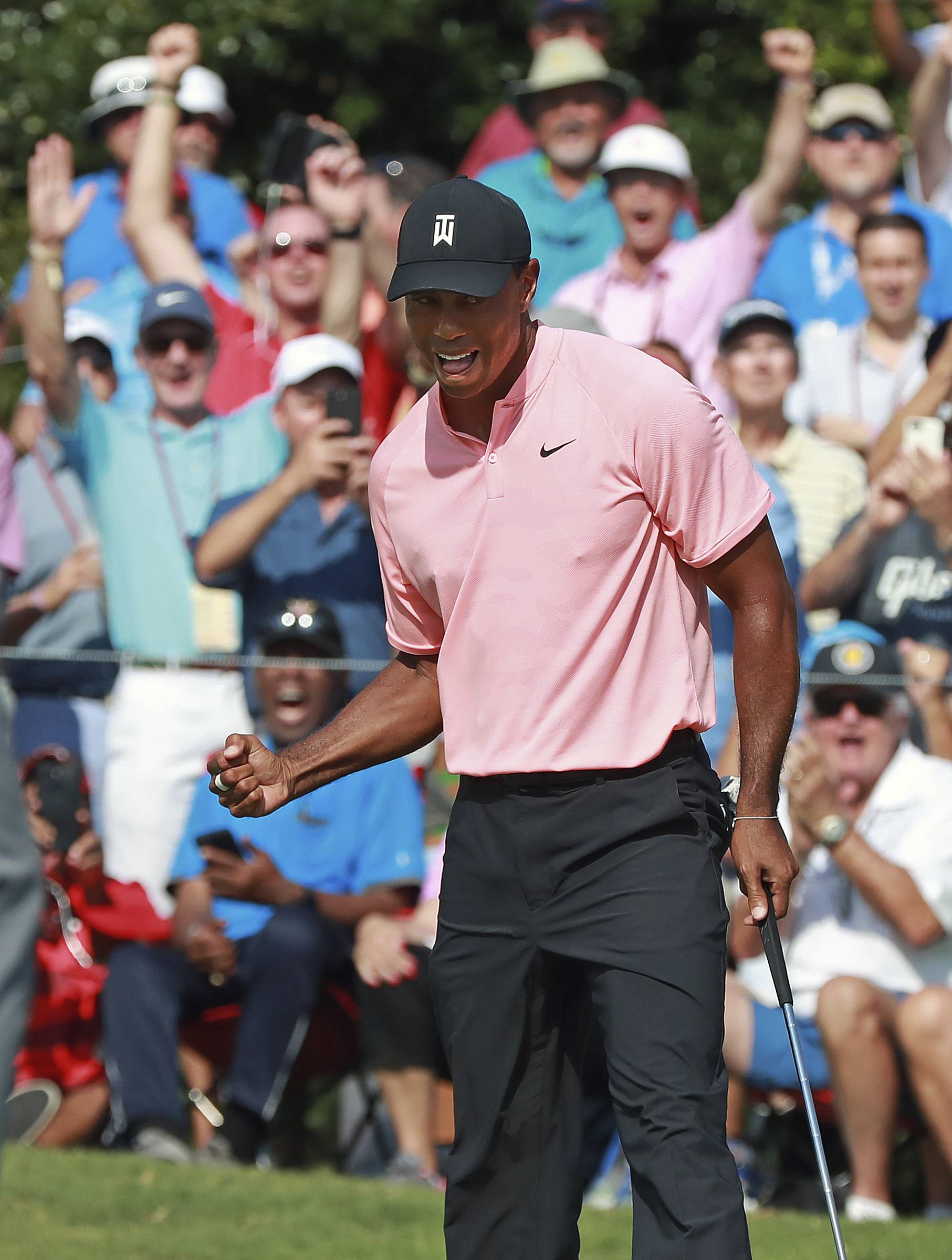 Tiger Woods eagled the 18th hole Thursday to grab a share of the first-round lead at the Tour Championship in Atlanta.