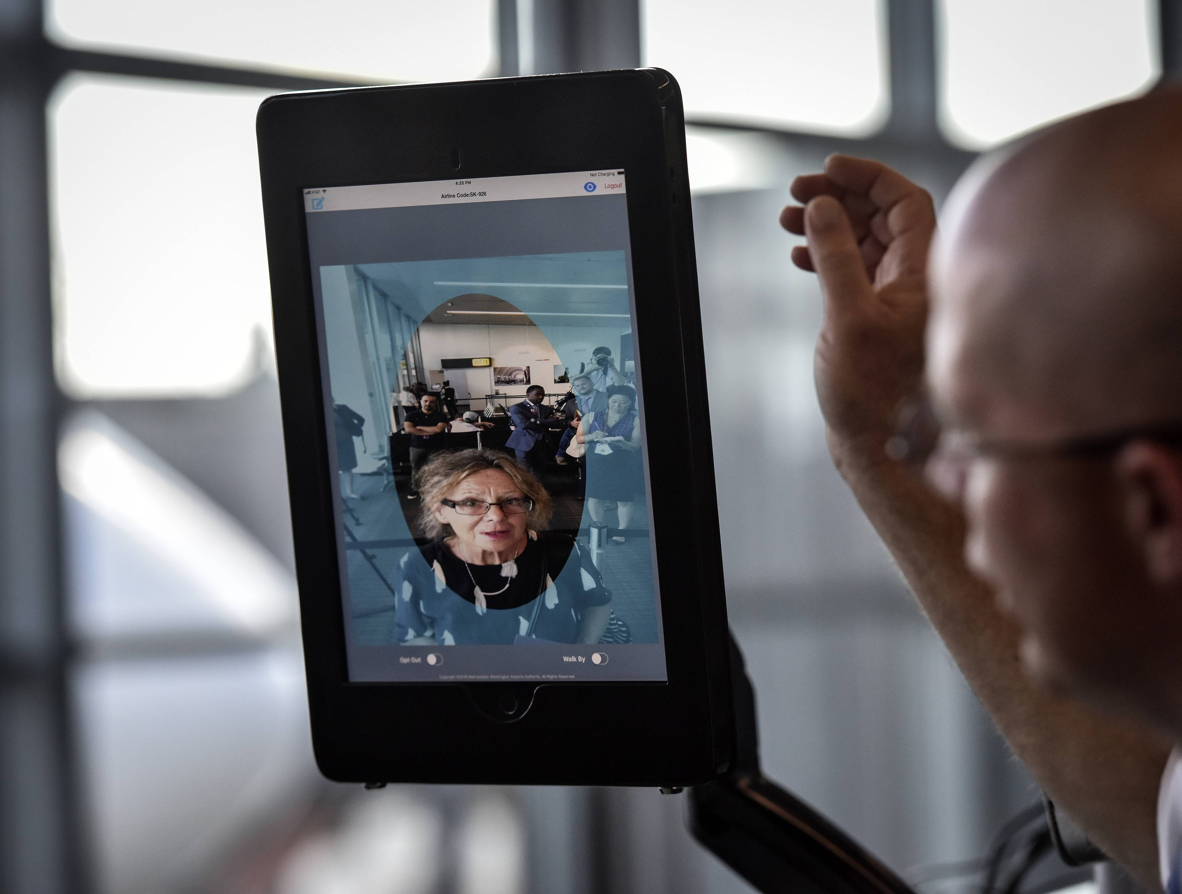 Station manager Chad Shane of SAS Airlines takes a traveler through the scanning process at Dulles International Airport. The facial scans can be compared with stored passport and visa photos.
