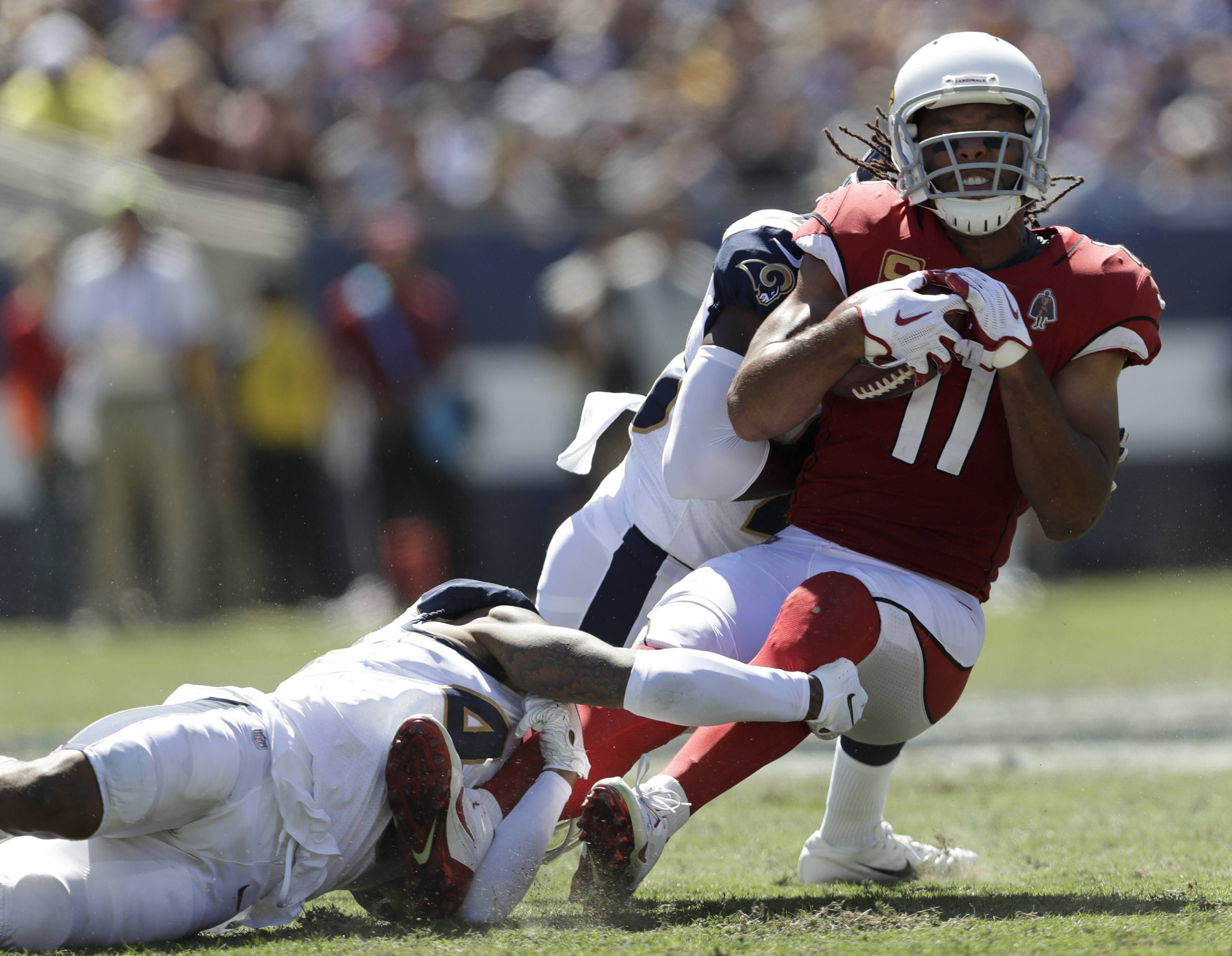 Arizona Cardinals wide receiver Larry Fitzgerald, right, is tackled by Los Angeles Rams defensive back John Johnson, bottom, and defensive back Lamarcus Joyner during the first half of an NFL football game Sunday, Sept. 16, 2018, in Los Angeles. (AP Photo/Marcio Jose Sanchez)