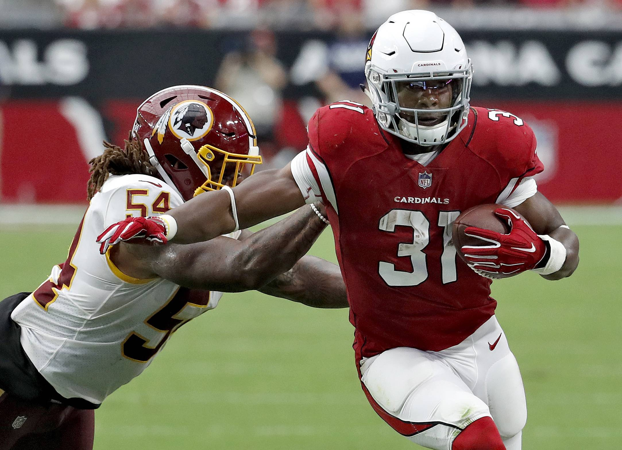 FILE — In this Sept. 9, 2018, file photo, Arizona Cardinals running back David Johnson (31) is hit by Washington Redskins linebacker Mason Foster (54) during the second half of an NFL football game, in Glendale, Ariz. The 0-2 Cardinals face the Chicago Bears on Sunday. (AP Photo/Rick Scuteri, File)