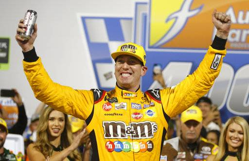 Kyle Busch (18) celebrates winning the NASCAR Cup Series auto race in victory lane at Richmond Raceway in Richmond, Va., Saturday, Sept. 22, 2018. (AP Photo/Steve Helber)