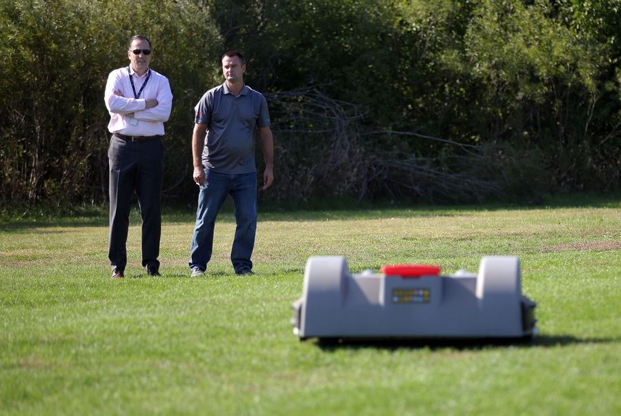Lake Zurich District 95 Superintendent Kaine Osburn, left, and Mark Kropiwiec of Echo Product Support watch a robotic mower cut the grass at Lake Zurich High School Friday.