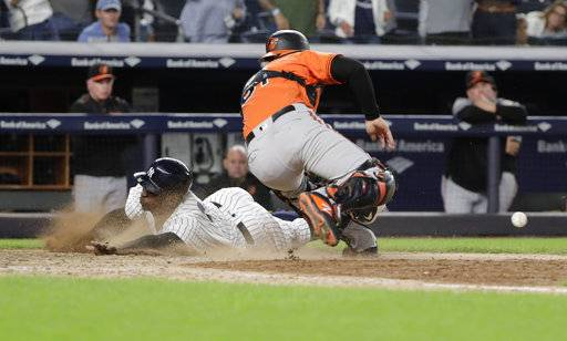 New York Yankees' Didi Gregorius slides past Baltimore Orioles catcher Caleb Joseph to score during the eleventh inning of a baseball game Saturday, Sept. 22, 2018, in New York. The Yankees won 3-2.