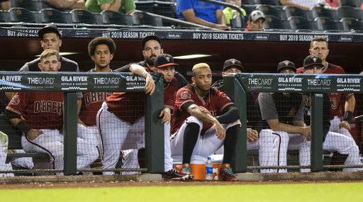 Arizona Diamondbacks players watch the last out of a basseball game against the Colorado Rockies which officially eliminated them from postseason Sunday, Sept 23, 2018, in Phoenix.
