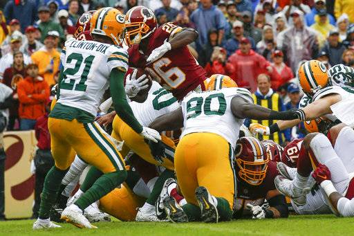 Washington Redskins running back Adrian Peterson (26) carries the ball into the end zone for a touchdown during the first half of an NFL football game against the Green Bay Packers, Sunday, Sept. 23, 2018, in Landover, Md. (AP Photo/Alex Brandon)