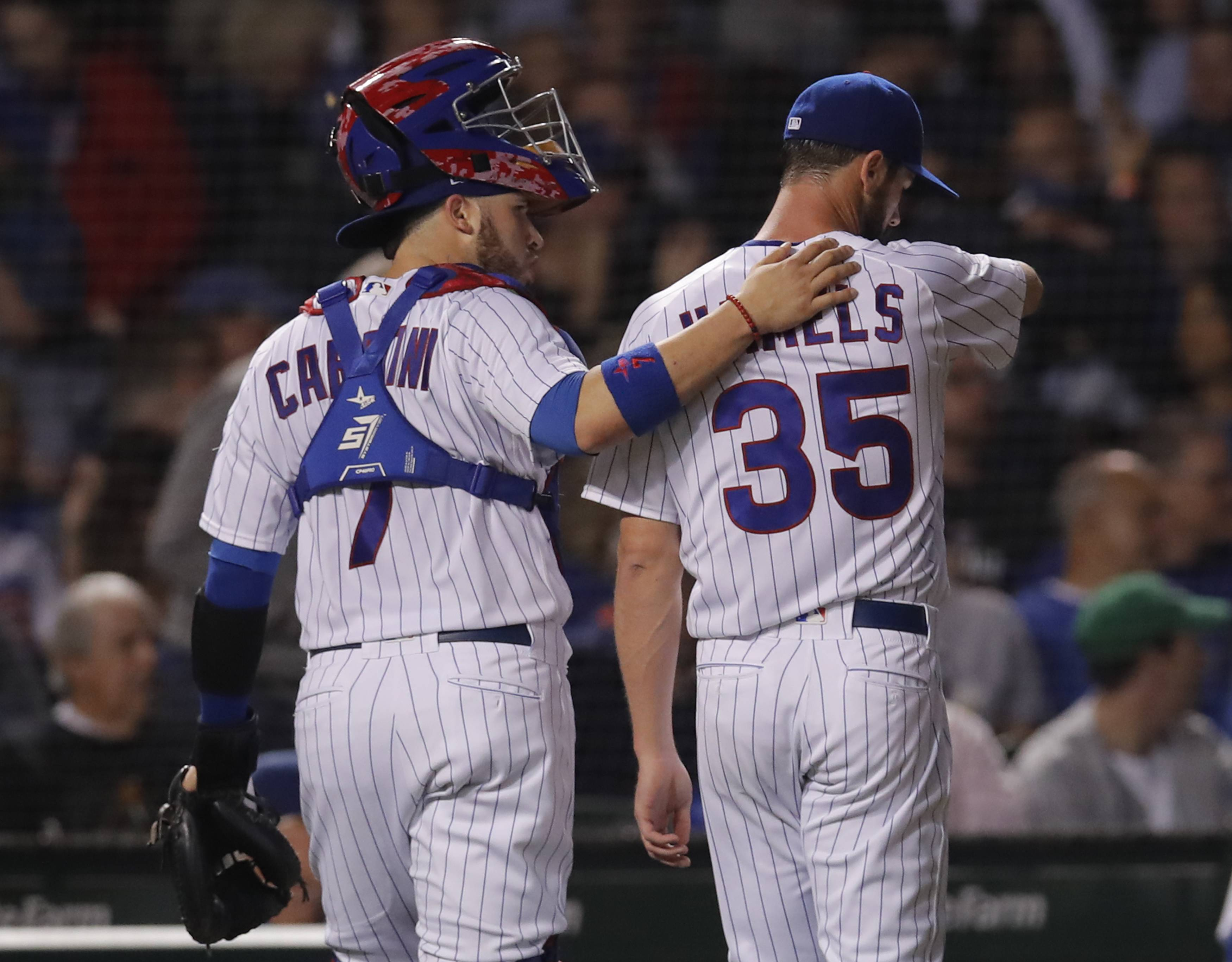 Chicago Cubs' Victor Caratini, left, walks back to the dugout with Cole Hamels at the end of the third inning of a baseball game against the Pittsburgh Pirates, Monday, Sept. 24, 2018, in Chicago. (AP Photo/Jim Young)