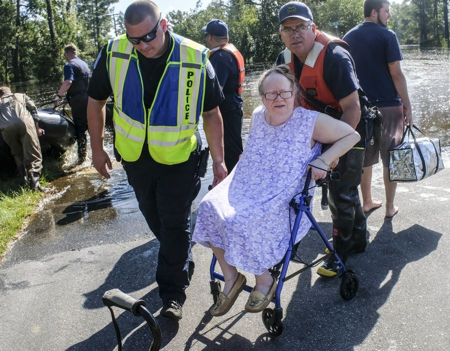 Coastguardsmen and Conway Police help Denise Fulmer from her flooded Busbee Street home on Sunday, Sept. 23, 2018, where she would be relocated to a shelter at Conway Recreation Center. The Sherwood Drive area of Conway, S.C., began to look like a lake on Sunday as homes were submerged deeper than ever in flood waters that have already set historic records.  (Jason Lee/The Sun News via AP)