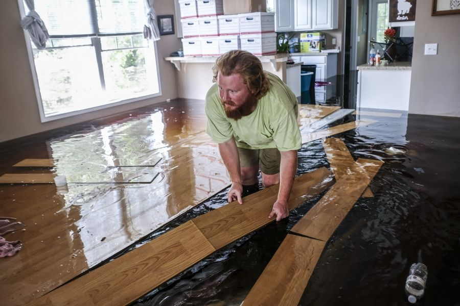 David Covington moves floating floor boards out of his path inside his flooded Conway, S.C. home on Sunday, Sept. 23, 2018. The Sherwood Drive area of Conway, S.C., began to look like a lake on Sunday as homes were submerged deeper than ever in flood waters that have already set historic records.  (Jason Lee/The Sun News via AP)