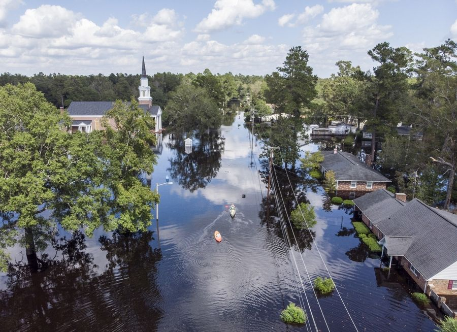 Kayaks are paddled up Long Avenue past flooded sections of the Sherwood Drive community of Conway, S.C., Sunday, Sept. 23, 2018 as homes were submerged deeper than ever in flood waters that have already set historic records.  (Jason Lee/The Sun News via AP)