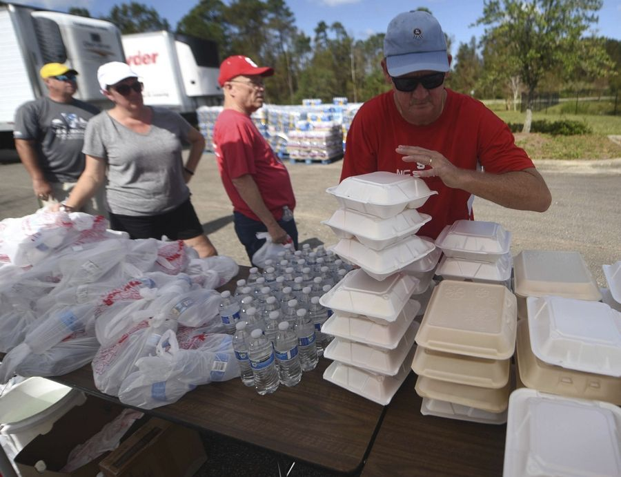 John Davis grabs meals to had out at the NC Baptist Men's relief site at First Baptist Activity Center in Wilmington N.C., Sunday, September 23, 2018. The organization was distributing more than 16,000 meals on Sunday.(Matt Born/The Star-News via AP)