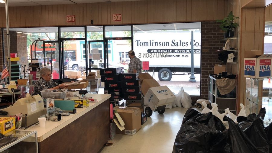 Employees at Tomlinson Department Store take all the merchandise out of the store in Georgetown, South Carolina, on Monday, Sept. 24, 2018. Officials have been warning of record flooding in the area from Hurricane Florence for days. (Jeffrey Collins/Associated Press)