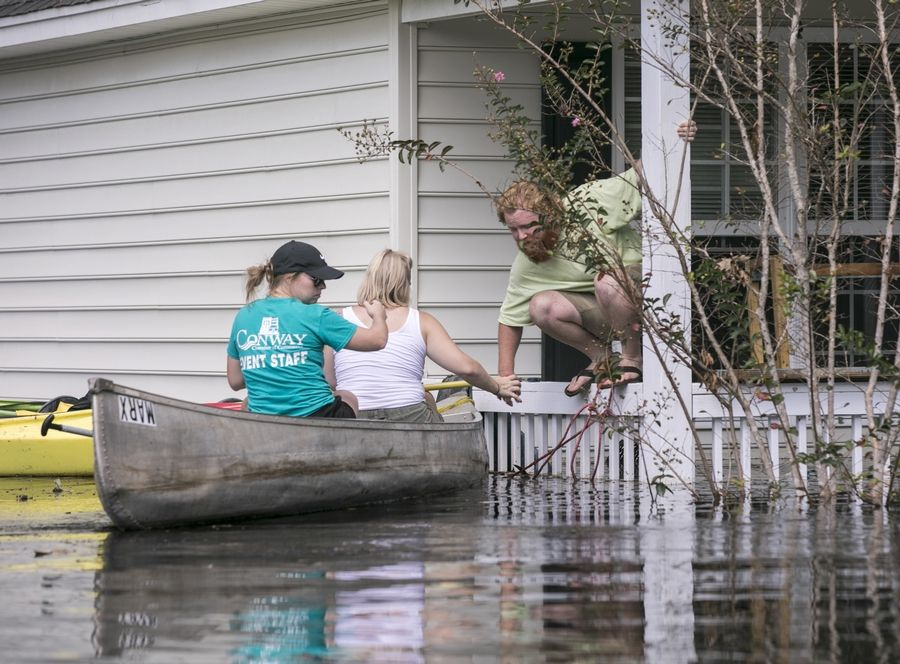 David Covington jumps from a porch railing to his canoe along with Maura Walbourne and her sister Katie Walborne in Conway, S.C., Sunday, Sept. 23, 2018. The three paddled a canoe to Covington's home on Long Avenue on Sunday to find it flooded and the floor boards floating. (Jason Lee/The Sun News via AP)