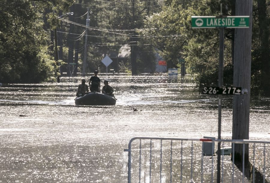 United States Coastguardsmen navigate an inflatable boat up Sherwood Drive in Conway, s.c., checking on residents on Sunday, Sept. 23, 2018. records.  (Jason Lee/The Sun News via AP)