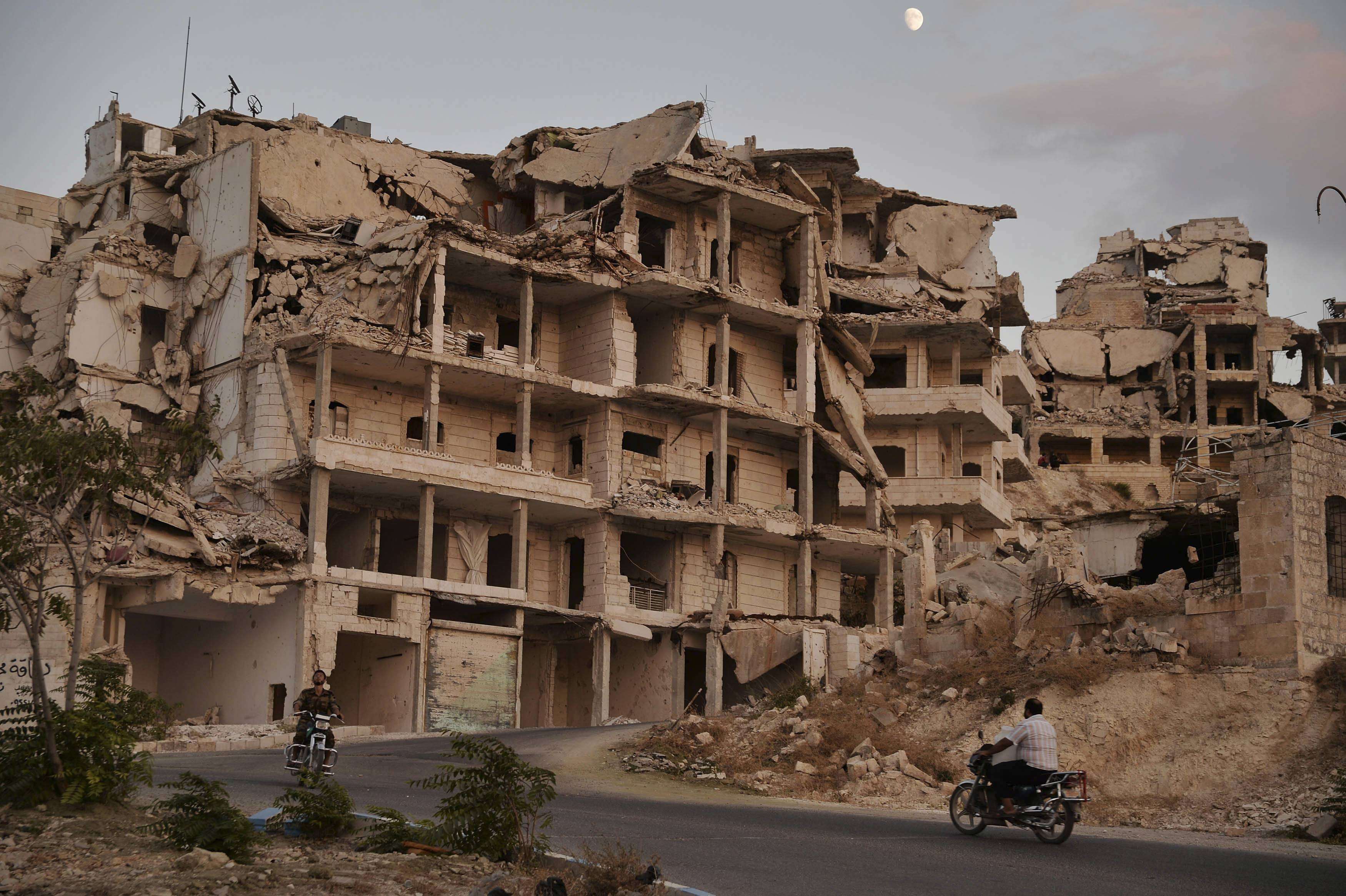 FILE - In this Sept. 20, 2018, file photo, motor cycles ride past buildings destroyed during the fighting in the northern town of Ariha in Idlib province, Syria. As world leaders talk peace at the U.N. this week, the Syrian region of Idlib clings to fragile hope that diplomacy will help avert a blowout battle over the country's last rebel stronghold. (Ugur Can/DHA via AP, File)