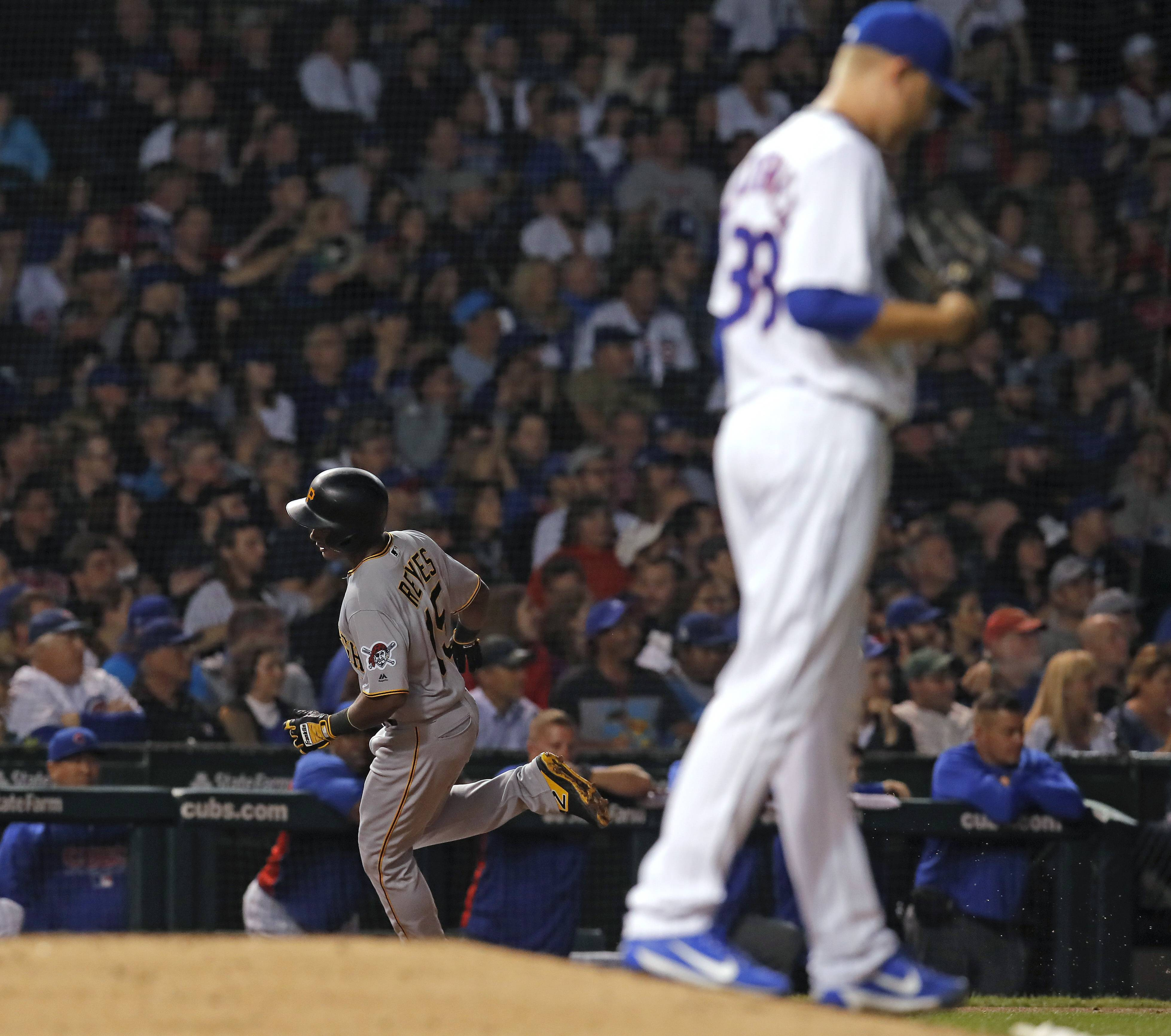 Pittsburgh Pirates' Pablo Reyes, left, rounds the bases after hitting a three-run home run off Chicago Cubs' Mike Montgomery, foreground, during the second inning of a baseball game Tuesday, Sept. 25, 2018, in Chicago. (AP Photo/Jim Young)