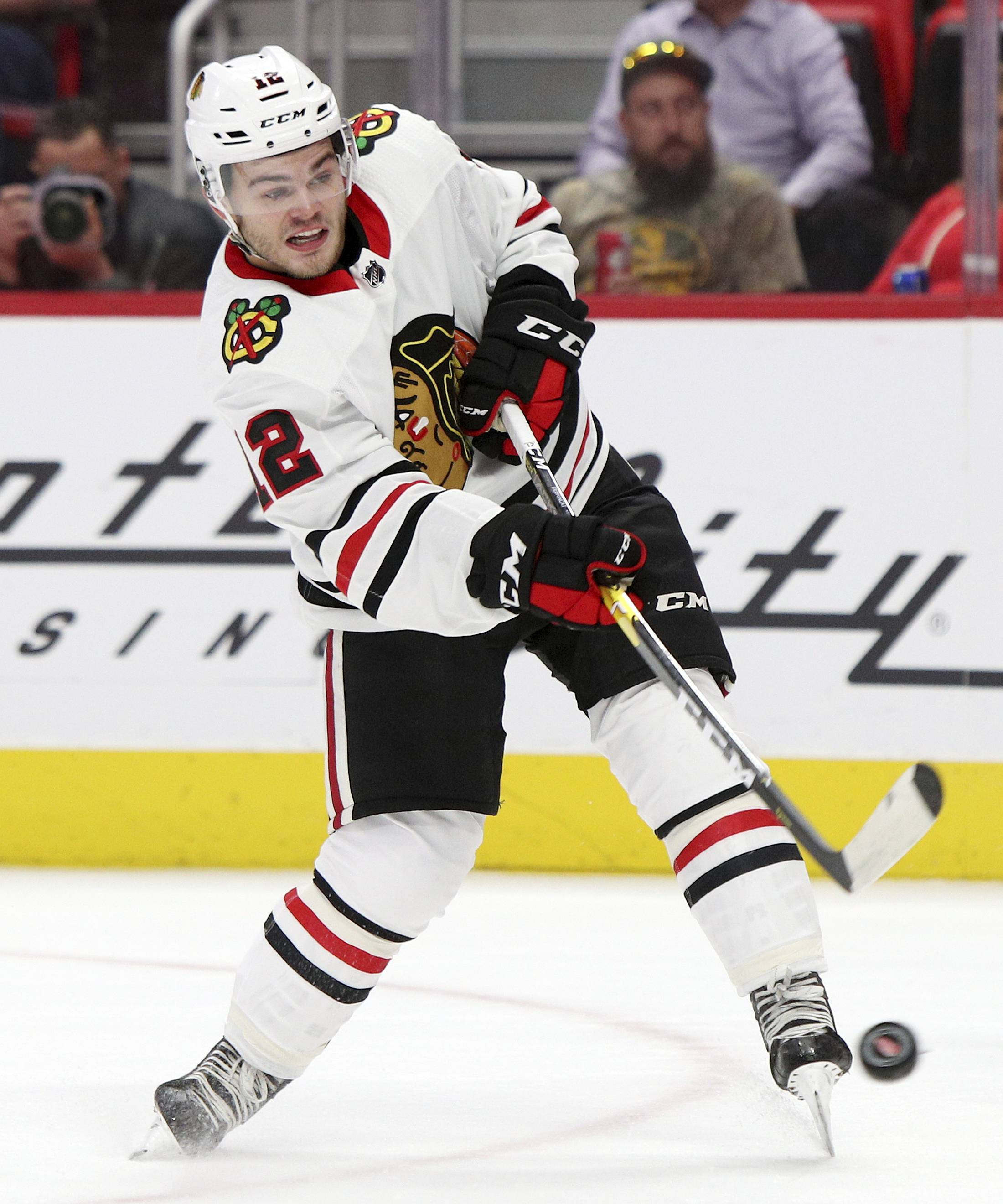Chicago Blackhawks forward Alex DeBrincat (12) shoots the puck during the first period of a preseason NHL hockey game against the Detroit Red Wings, Thursday, Sept. 20, 2018 in Detroit. (Mike Mulholland/The Grand Rapids Press via AP)