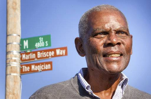 FILE - In this Oct. 22, 2014, file photo, Marlin Briscoe stands in front of a street that was renamed for him in Omaha, Neb. The Pro Football Hall of Fame calls the Omaha, Neb. native the first black quarterback in the modern era of pro football. He opened the door for many, including Carolina's Cam Newton and Seattle's Russell Wilson, who both pay homage to him. (Kent Sievers/Omaha World-Herald via AP, File)