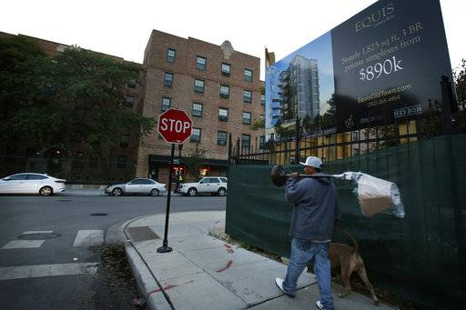In this Thursday, Aug. 24, 2017, photo, a man carrying a lamp walks past an advertisement board for new apartments in Chicago's Old Town neighborhood. Marshall Field Garden Apartments, subsidized housing, in background, sits on the west side of Sedgwick Street. Expensive homes and condos are continuing to rise up on the east side of the street, with one such building planned for this corner.