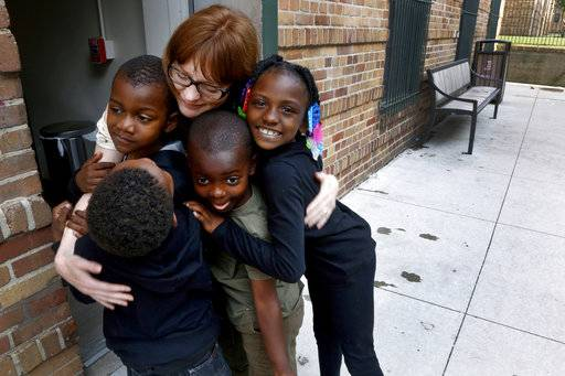 "In this Monday, June 25, 2018, photo, Charlie Branda, founder of Art on Sedgwick, hugs a few young residents of Marshall Field Garden Apartments in Chicago. Branda, whom many children call ""art teacher,"" is a former commercial banker who left the profession to raise her two children, now teens. Though she doesn't consider herself an artist, she later opened a neighborhood art studio called Art on Sedgwick to try to unite a neighborhood divided by income and race. Her neighbors are often surprised to learn that, while she lives on the wealthier side of the neighborhood, she was raised by a single mom with modest means."