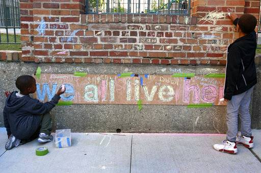 "In this Friday, June 1, 2018, photo, two boys help finish a chalk mural at Marshall Field Garden Apartments during the Art on Sedgwick annual art show in Chicago. The theme of the mural ""We all live here"" was conceived by artist Rich Alapack who has focused the public art project at schools and community centers. ""It's really a simple message -- but things are so divided,"" Alapack says. He said the goal is to bring people together. ""Sometimes art can do that better than conversation."""