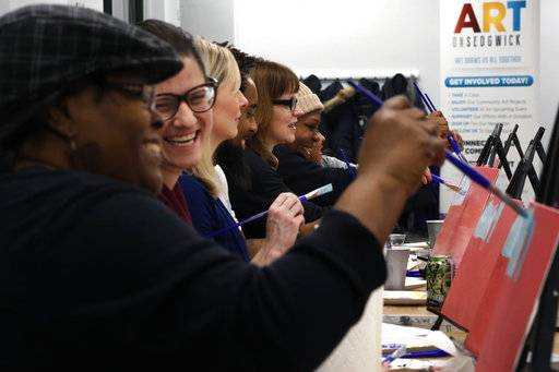 "In this Saturday, Feb. 10, 2018, photo, Adell Thomas, left, cracks a joke during a ""Sip and Paint"" class for adults at Art on Sedgwick, in Chicago. The class brings people from different backgrounds together to socialize. Art on Sedgwick was founded by Charlie Branda, center in glasses, as a way to unify a neighborhood that is divided by income and race. The core group of regulars is one of the studio's successes. ""But we're nowhere near where I want us to be,"" says Thomas, who has become a board member at Art on Sedgwick."