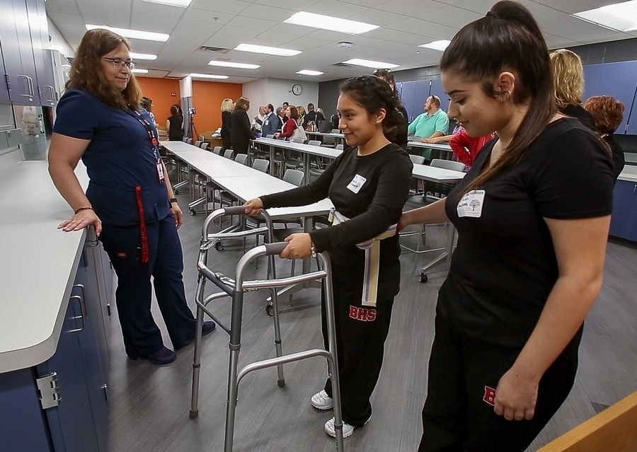 Kelly Allen, left, an instructor and practicing nurse, watches as seniors Angelica Elizarraraz, center, and Citlalli Salazar practice with a walker Thursday during the opening of the health sciences laboratory at Barrington High School.