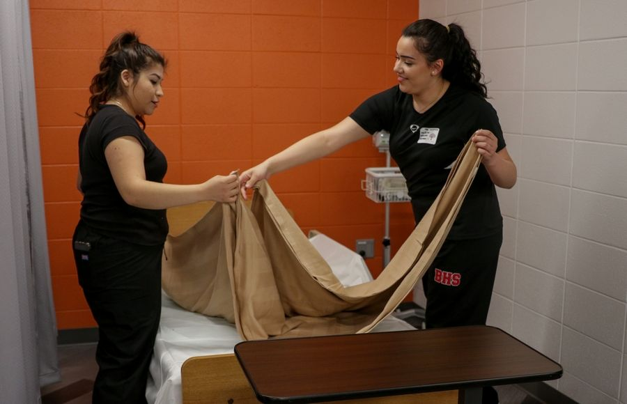 Hilary Perez, left and Jocelyn Sanchez, both seniors, work at bed making Thursday at the new health sciences laboratory at Barrington High School.