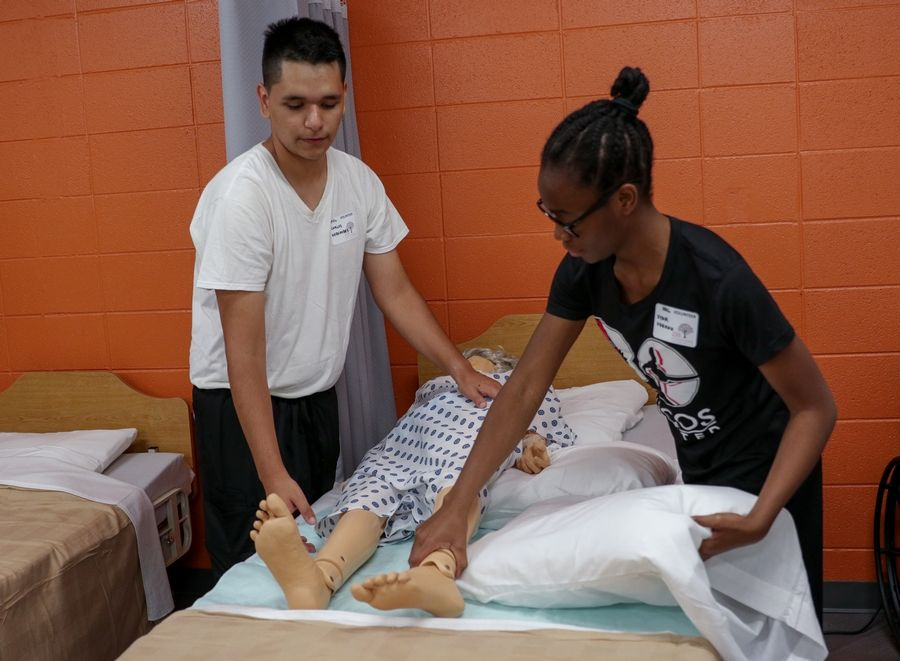 "Seniors Carlos Hernandez and Star Udeogu work at helping a ""patient"" Thursday as the health sciences laboratory at Barrington High School was unveiled. Students can get a head start on learning basic nursing skills."