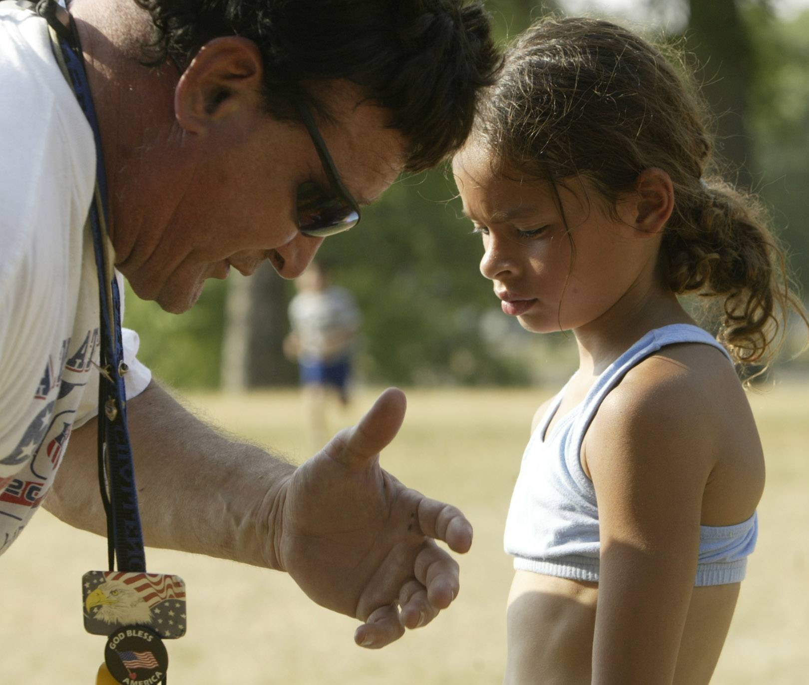 Bob Pleticha, head coach and founder of the Elgin Sharks Track Club, works with runner Shailey Rodriguez, 8, of Elgin, during practice at Channing Park in Elgin. Pleticha dedicated his life to teaching, coaching and mentoring Elgin-area youth. He died Sept. 27.