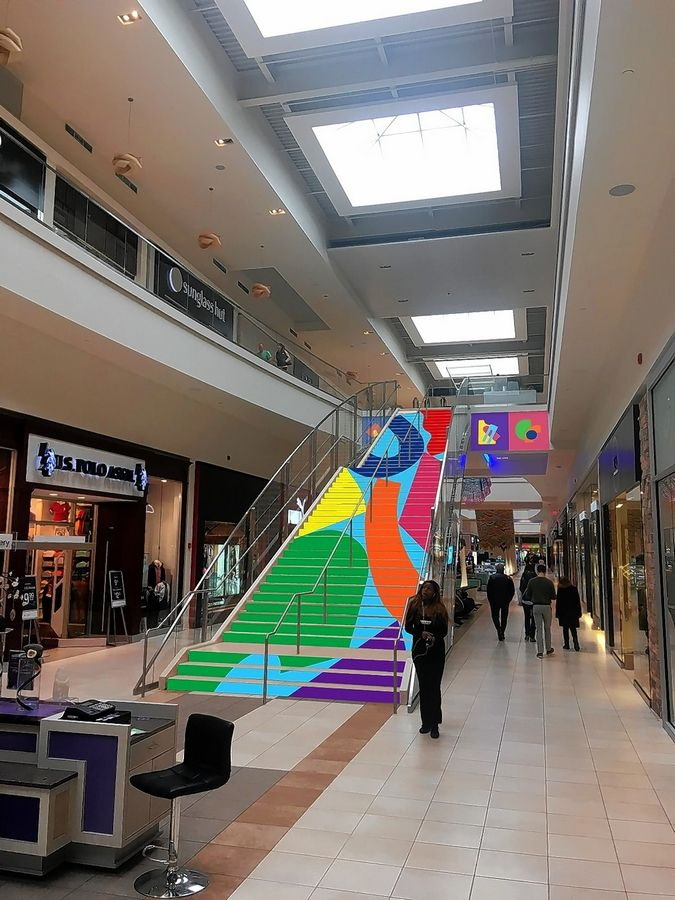 Artist Chad Kouri's installation of colorful shapes on the grand staircase of Fashion Outlets of Chicago is among the new art installations at the Rosemont mall.