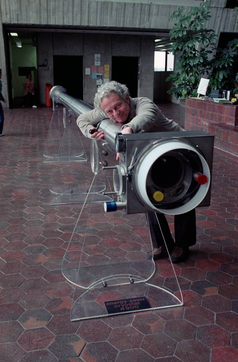 Leon Lederman poses with a cryostat in the atrium of Fermilab in April 1982.