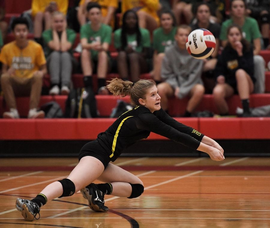 Fremd's Maddie Aichinger falls left to play the ball against Palatine Thursday in a girls volleyball match at Palatine High School.